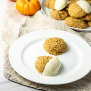 Pumpkin cookies on a plate, on dipped in white chocolate and the other plain - square