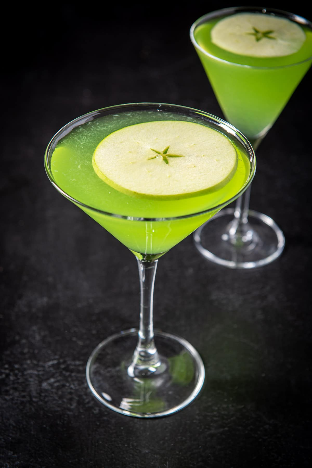 Close up of the apple floating in the sour appletini cocktail