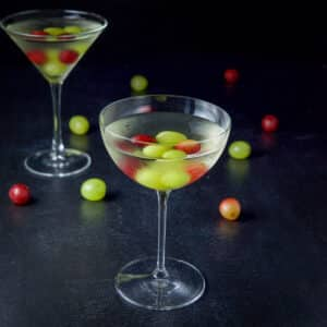 Bowl glass in front of the classic martini glass filled with the cocktail with grapes in the drink and on the table