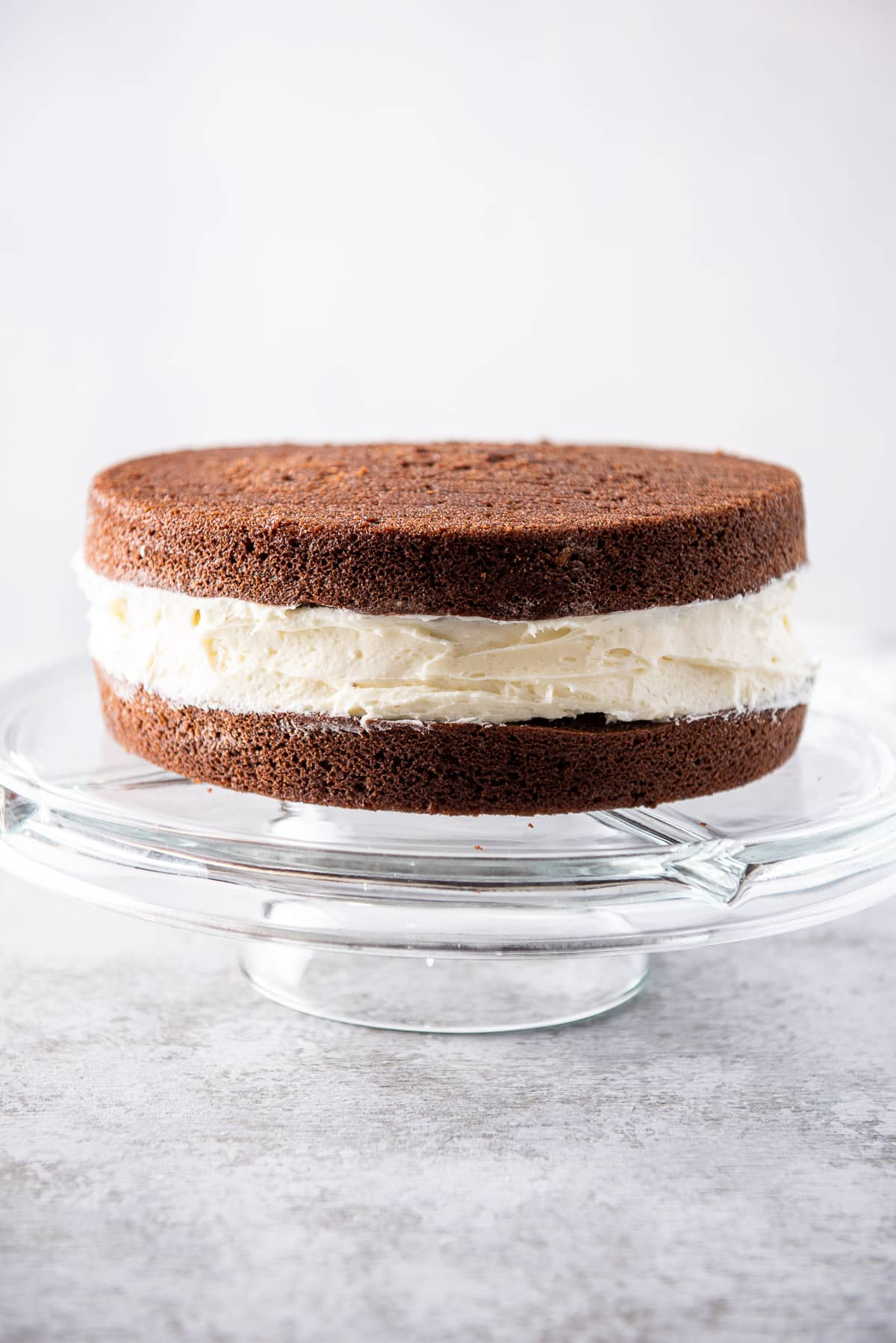 Vertical view of the chocolate cake with a big layer of frosting on a glass pedestal