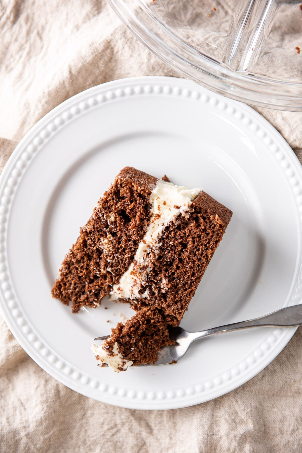 Overhead view of a white plate with a layered chocolate cake. There is a fork with a piece of cake on it