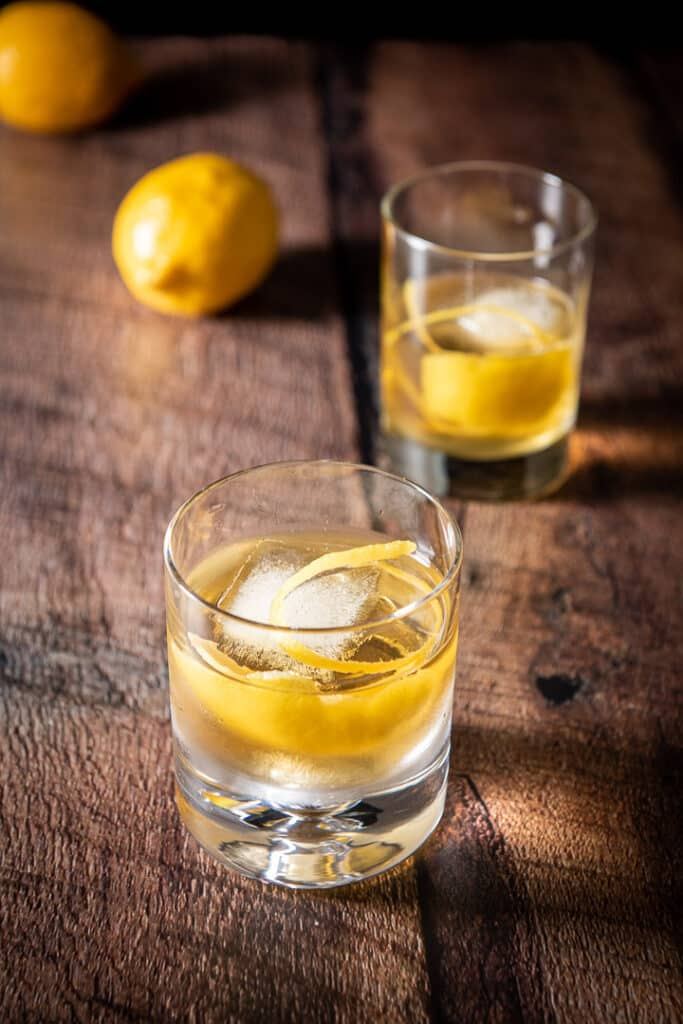 Two double old fashioned glasses filled with the rusty nail cocktail