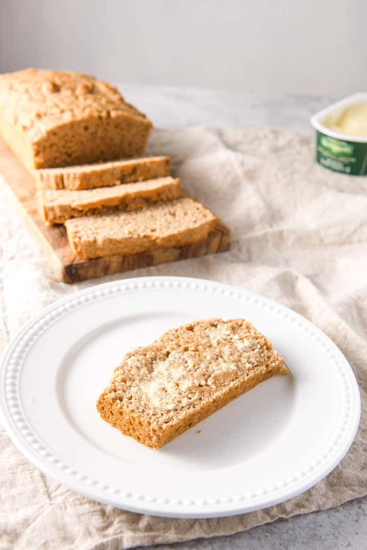A slice of beer bread that has butter slathered on it