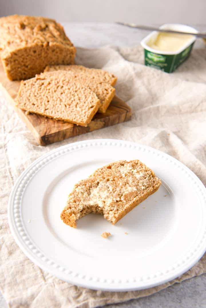A bite taken out of the bread on a white plate