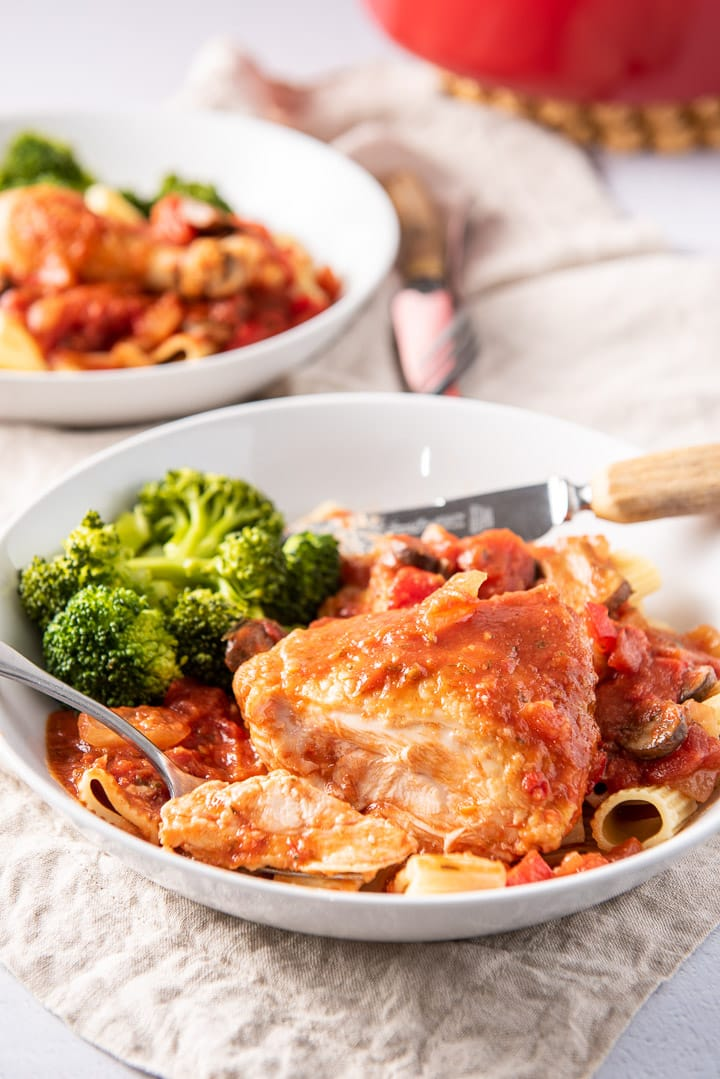 A forkful of chicken in a plate with the thigh and broccoli next to it