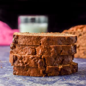 Four slices of date bread on top of each other with the loaf off to the right - square