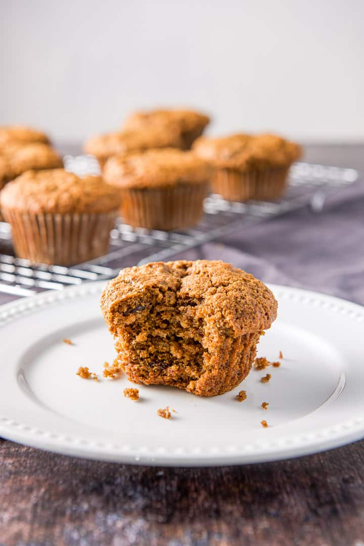 A bite taken out of one of the bran muffins on a plate