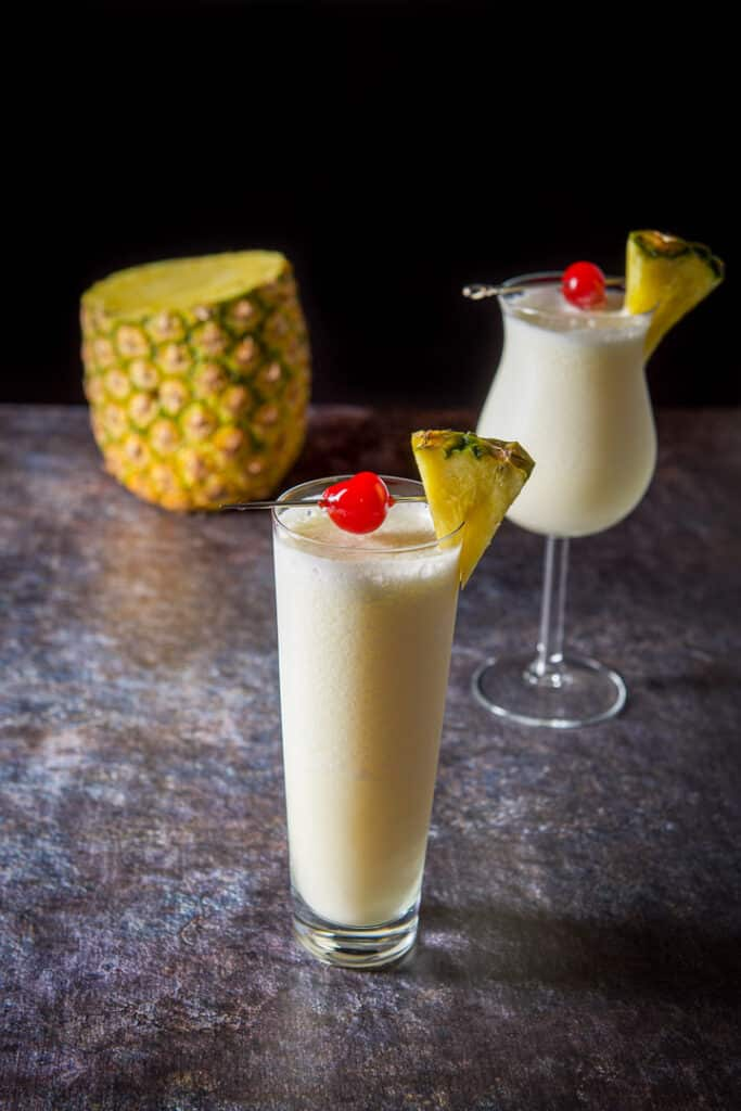 Two glasses with the pina colada with a most of a pineapple in the background