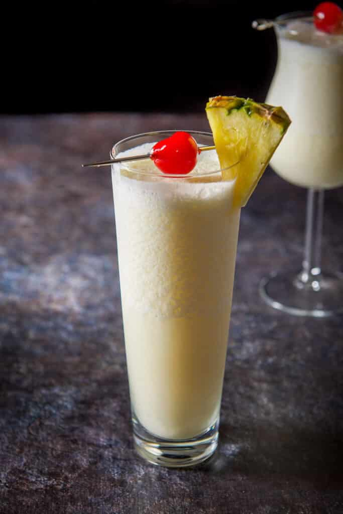 Tall glass of the pina colada in front of the tulip glass - garnished with a cherry and pineapple wedge