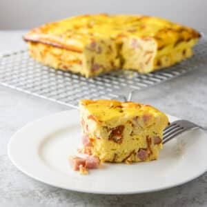 A white plate with a piece of eggy pizza gana with ham falling out of it and in the background there is the rest of it on a wire rack - square