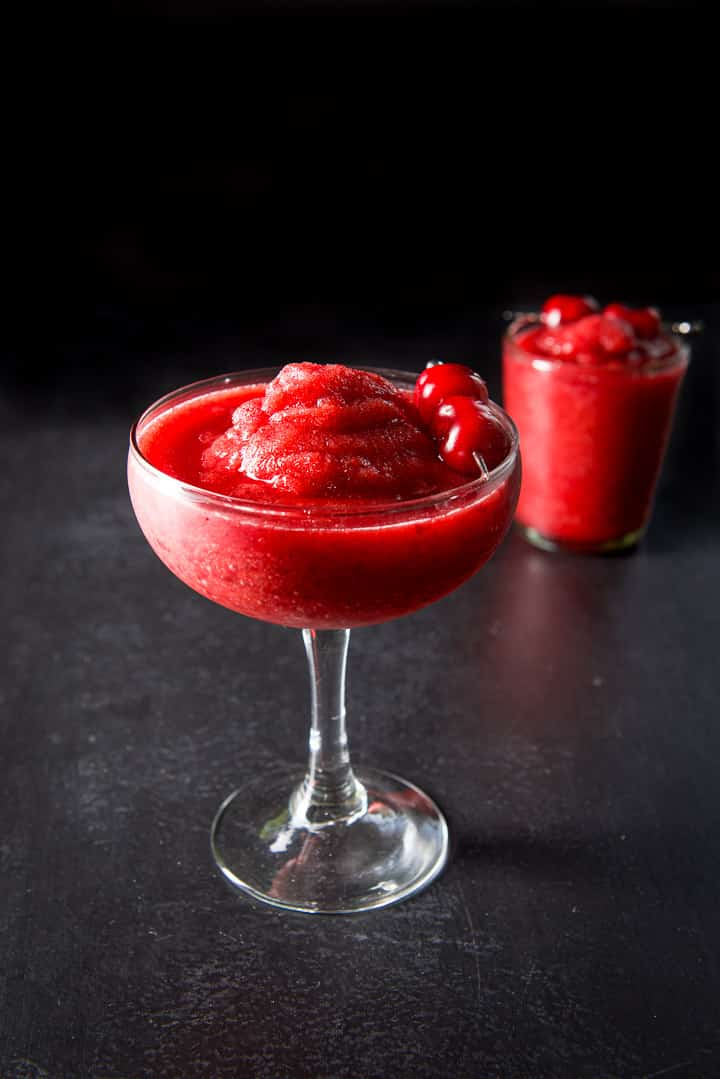 Bowl margarita glass overfilling with the frozen cherry marg with another glass off to the side