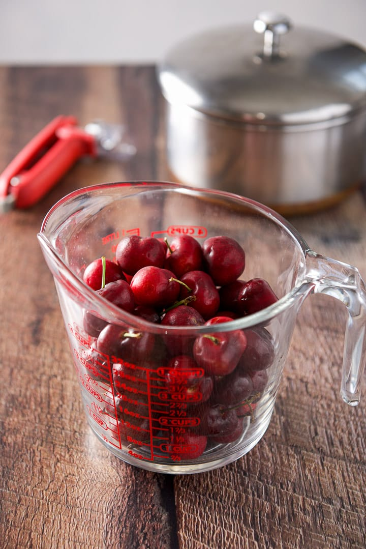 Cherries in a two cup measuring glass with a pitter and pan in the background