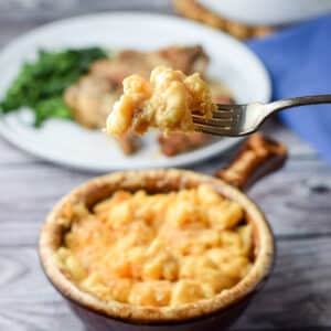 A forkful of cheesy macaroni over a crock filled with it