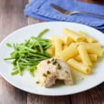 A boneless skinless piece of chicken on a plate with piccata sauce, capers, ziti and green beans