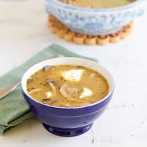 Mushroom soup in a blue bowl with sour cream in it. There is a lighter blue bowl filled with the soup in the background