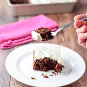 A fork holding a piece of chocolate cake above a plate