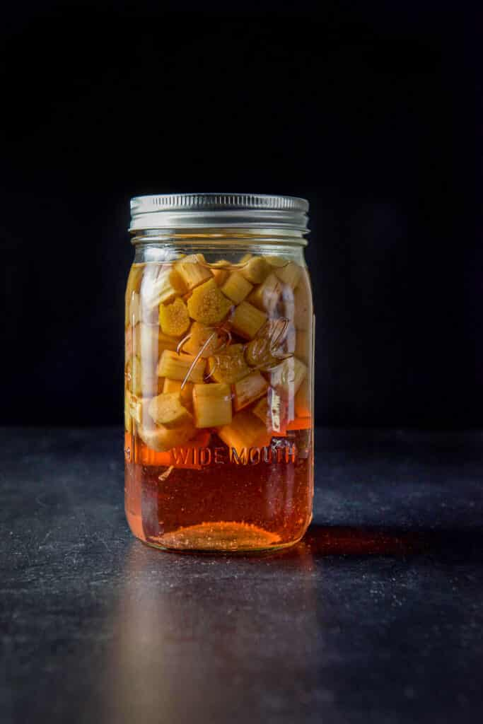 A jar of leeched rhubarb floating at the top and the red infused vodka on the bottom