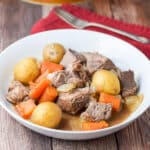 A round shallow bowl filled with the chuck roast with carrots and potatoes