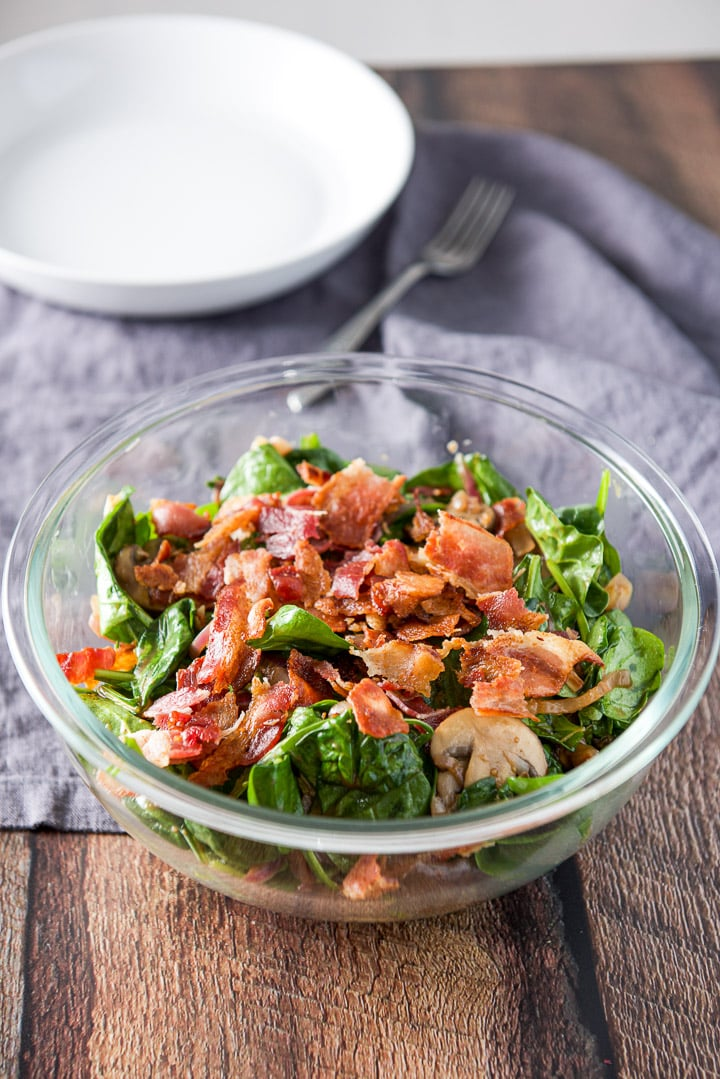 Clear bowl filled with the spinach salad with bacon crumbled on top. There is a white bowl in the background