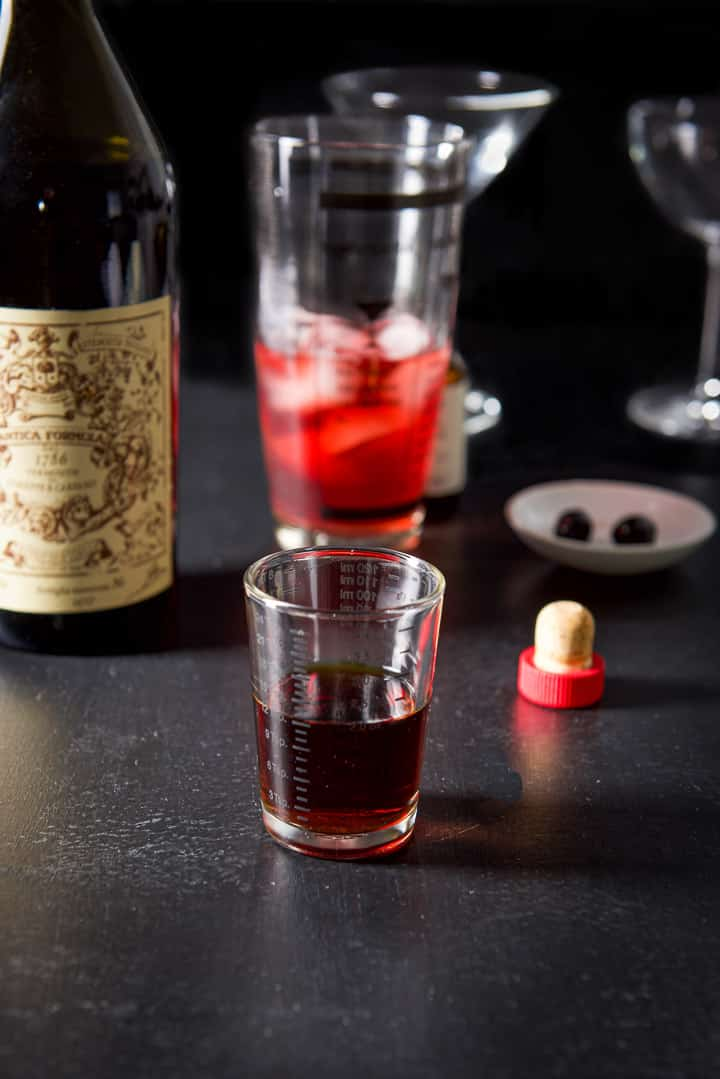 Sweet vermouth poured out with the bottle, half filled shaker, glasses and cherries in the background