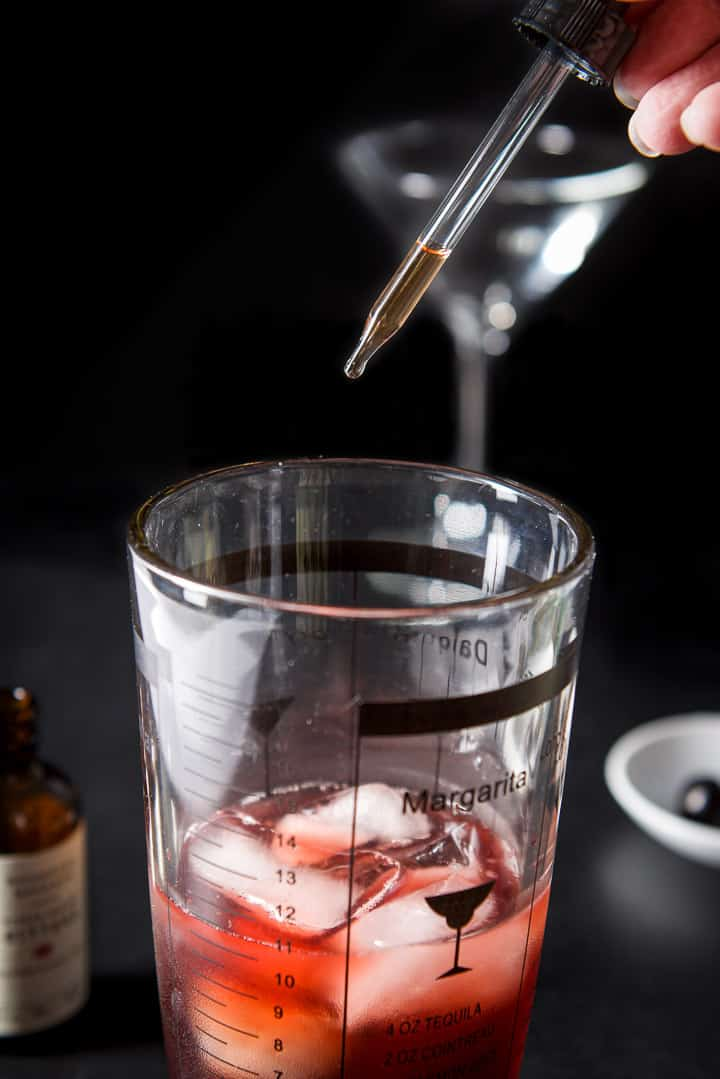 A hand holding a dropper filled halfway with cherry bitters over the cocktail shaker