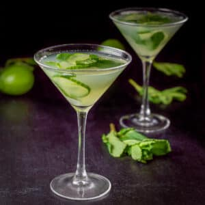 Two cucumber martinis in classic glasses with limes and mint in the background
