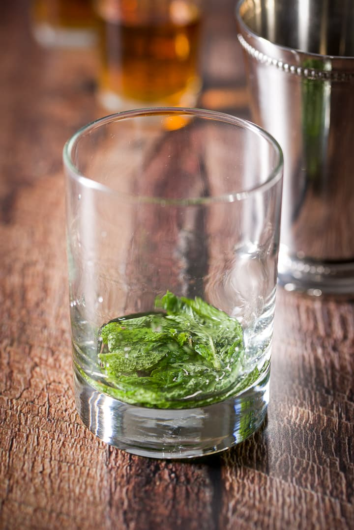 A clear glass and a stainless steel glass filled with the mint leaves and simple syrup muddled