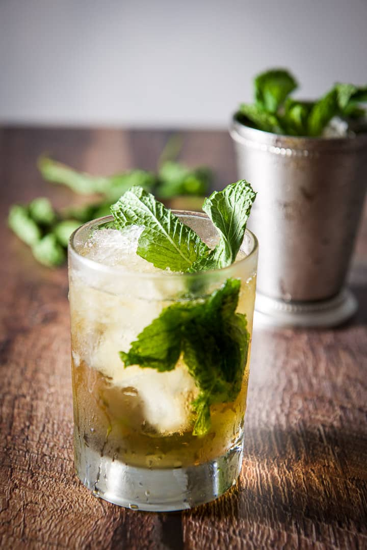 Clear glass filled with the julep with mint sticking out of it. The sterling silver glass is in the background