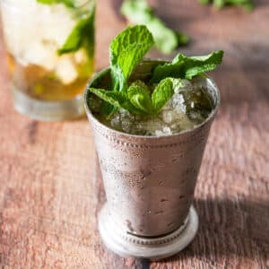 Square photo of a metal cup with the julep in it with fresh mint in as a garnish