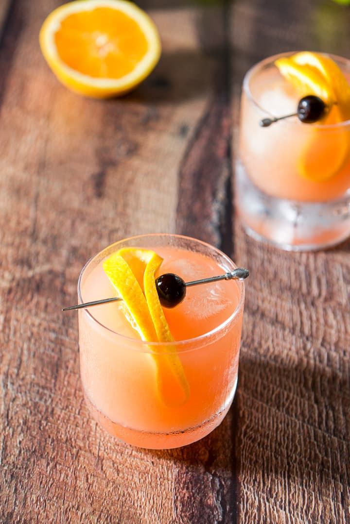 Two mai tais with slices of orange and cherries for garnish