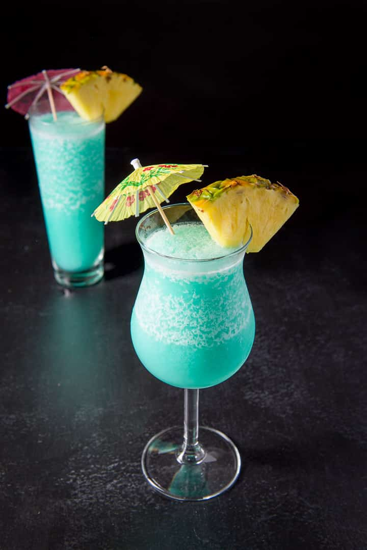 The tulip glass with the blue drink in front of the flared glass - garnished with pineapple and umbrellas