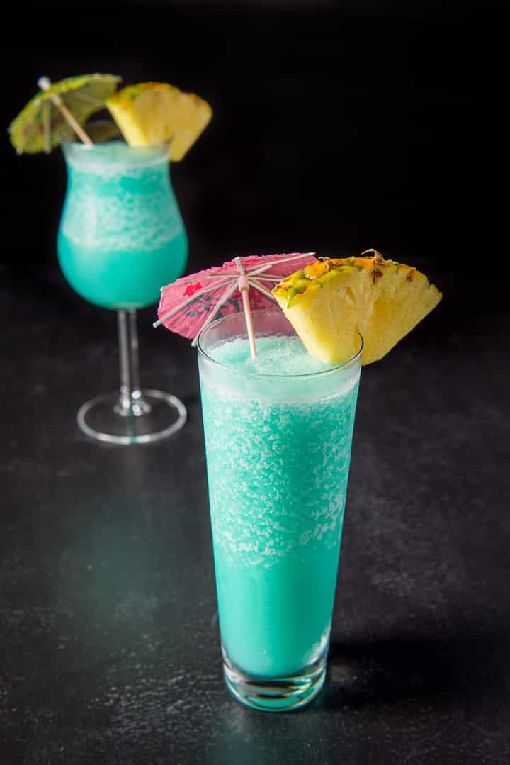 Flared glass filled with the frozen drink in front of the tulip glass. They are garnished with a pineapple wedge and umbrellas