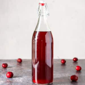 A tall bottle of cherry vodka with cherries on the table - square