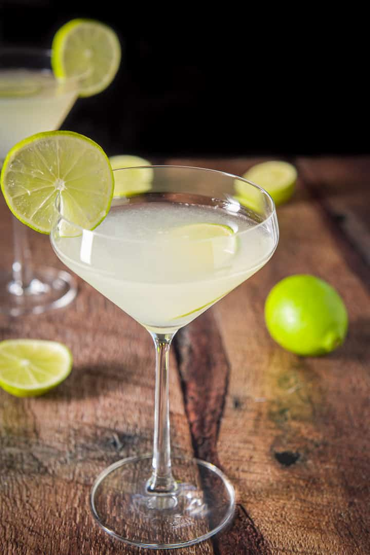 A curved martini glass with lime liquid garnished with lime wheels. There are also limes on the table and another glass in the background