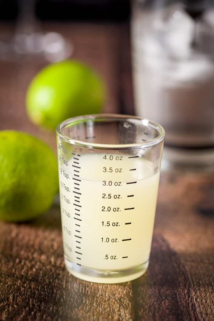 Lime squeezed out and measured with more limes and the shaker in the background