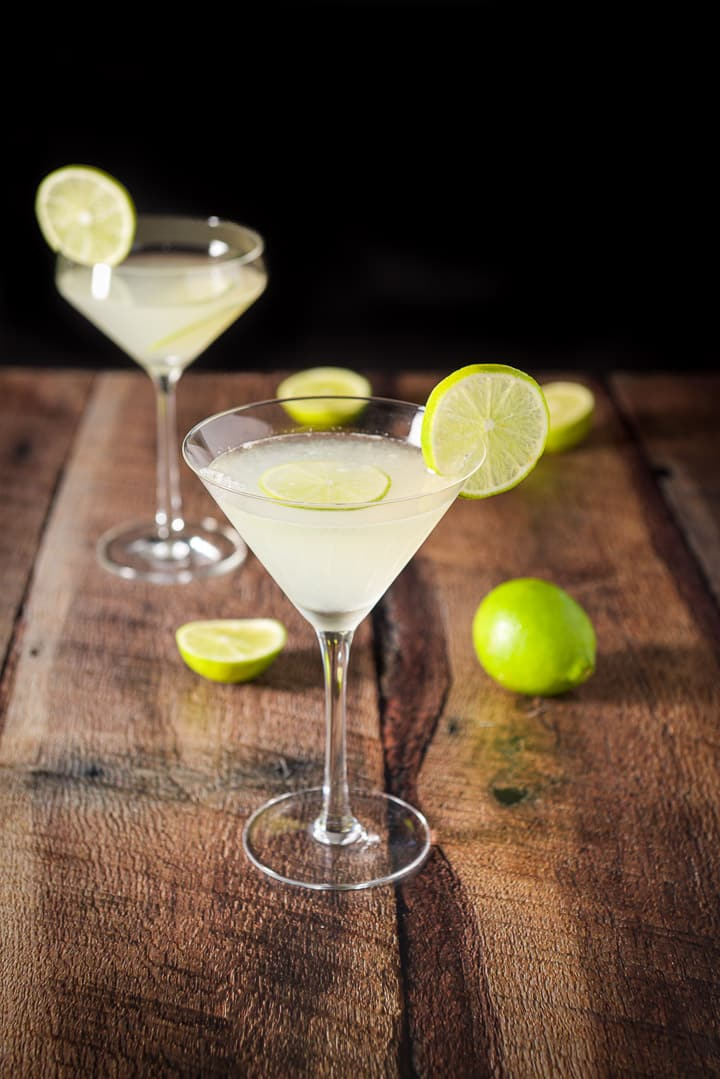 A beveled regular martini glass with another fun glass filled with the martini and garnished with lime wheels