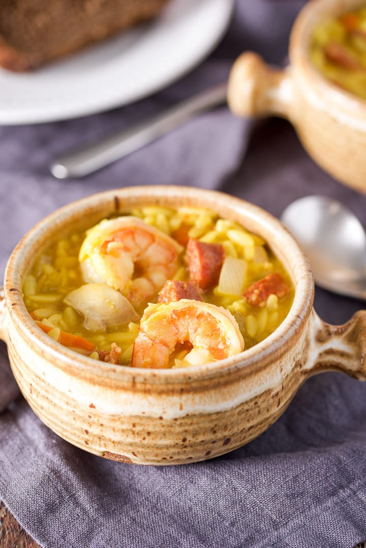 Close up of a beige crock with two shrimp, chorizo and orzo soup