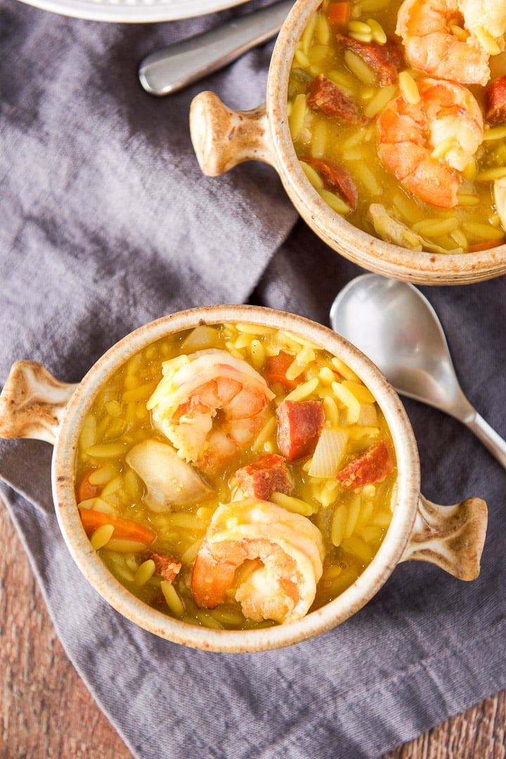 Overhead view of two crocks filled with a soup with lots of meat and orzo