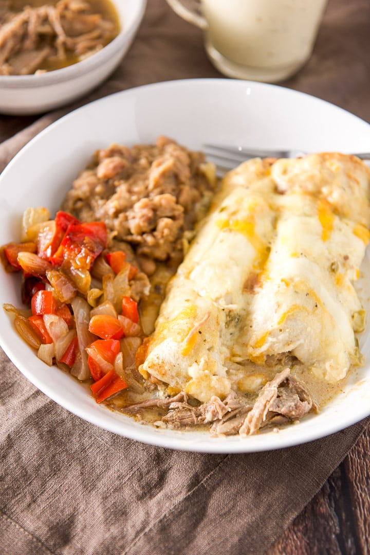 Two enchiladas with sour cream verde sauce with pork hanging out of them. There is also vegetables and beans on the plate