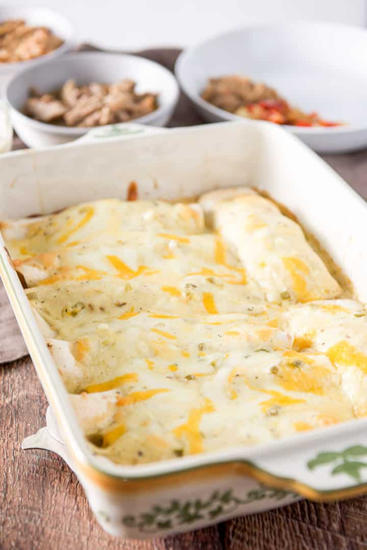 The enchiladas with sour cream sauce on the enchiladas in a baking dish and straight out of the oven. There are beans and pork in the background along with a plate