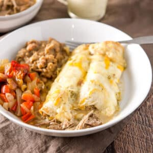 A white bowl with enchiladas with a cream sauce and beans and vegetable - square