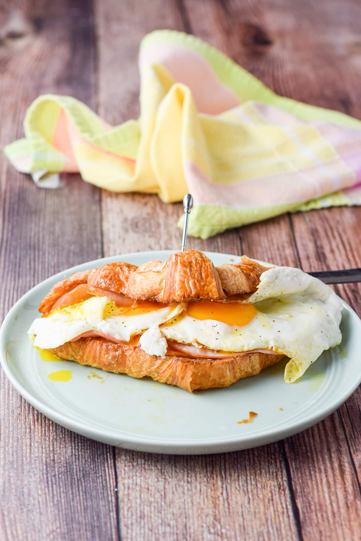 Eggs on a croissant with ham and cheese. There is a pick holding the croissant closed