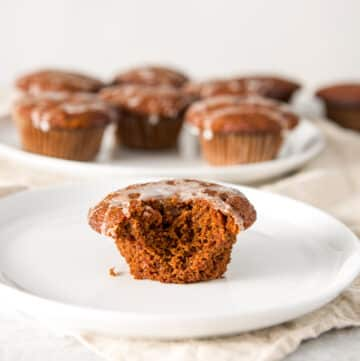 Ginger muffin on a plate with a bite taken out with a big plate of muffins in the background