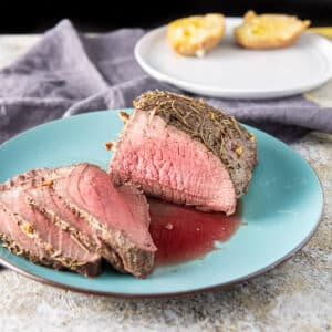 Blue platter with sliced roast beef with a white plate behind it with a potato on it - square