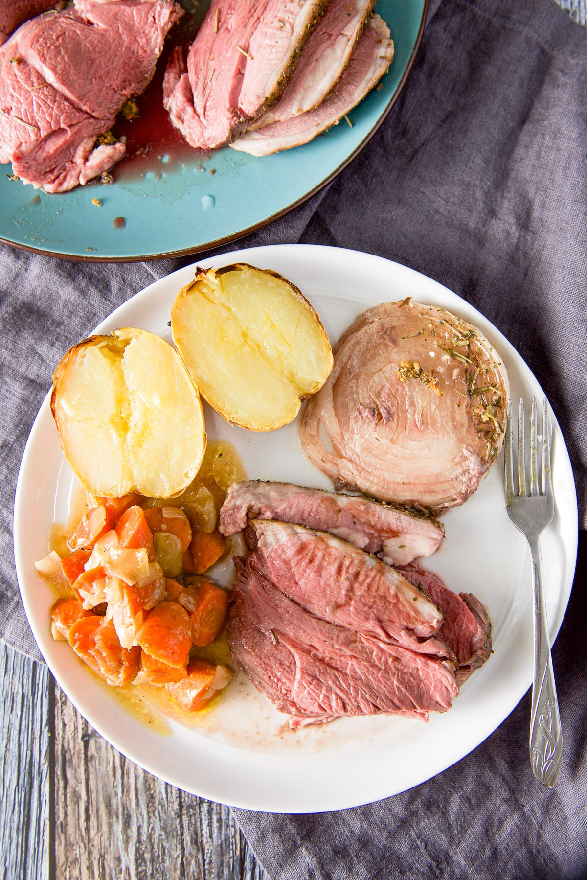 Overhead view of a white plate with a few slices of lamb, carrots, baked potato and onion