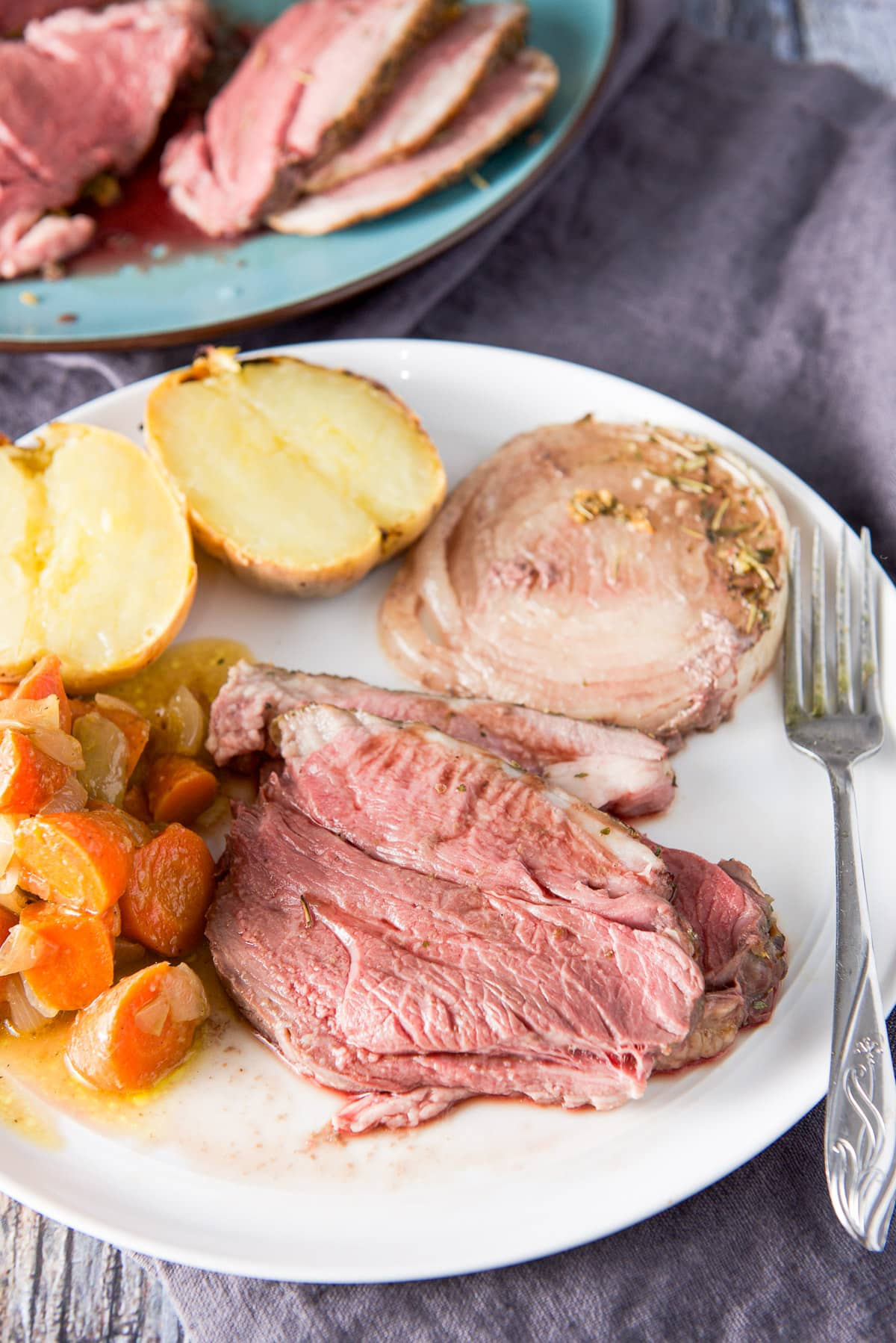 A white round plate with sliced lamb, onion, potato and carrots with the platter of the lamb in the background