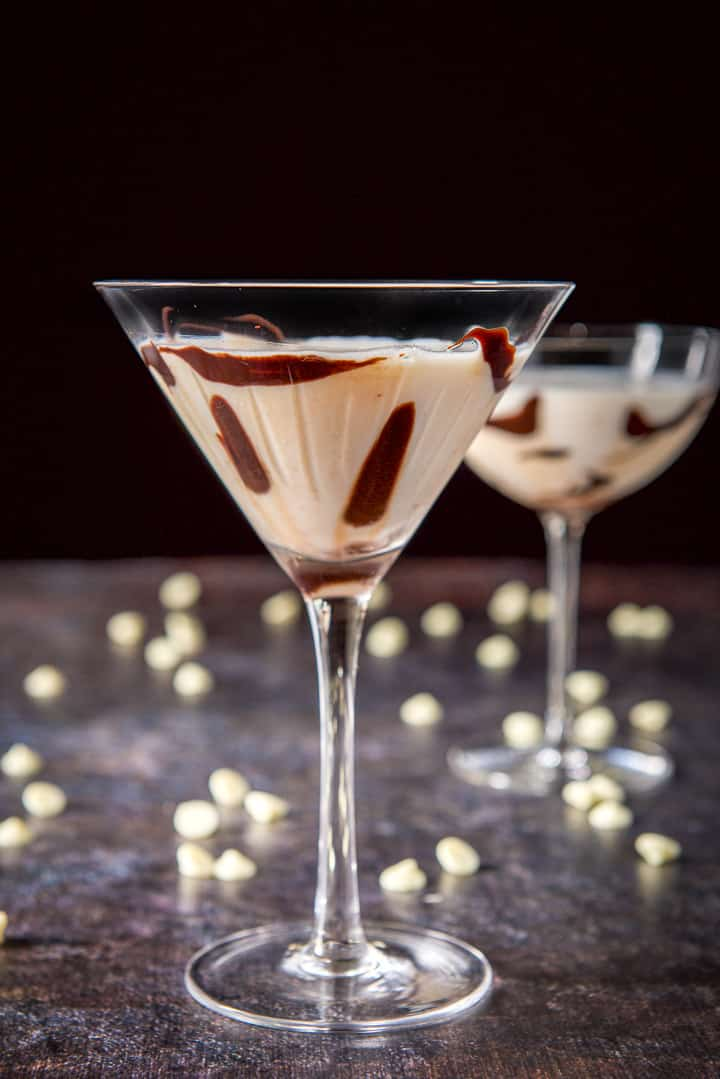 Classic martini glass filled with the white chocolate with more bits on the table