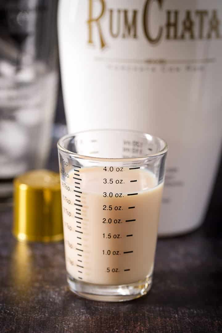 RumChata measured out with the bottle and shaker in the background