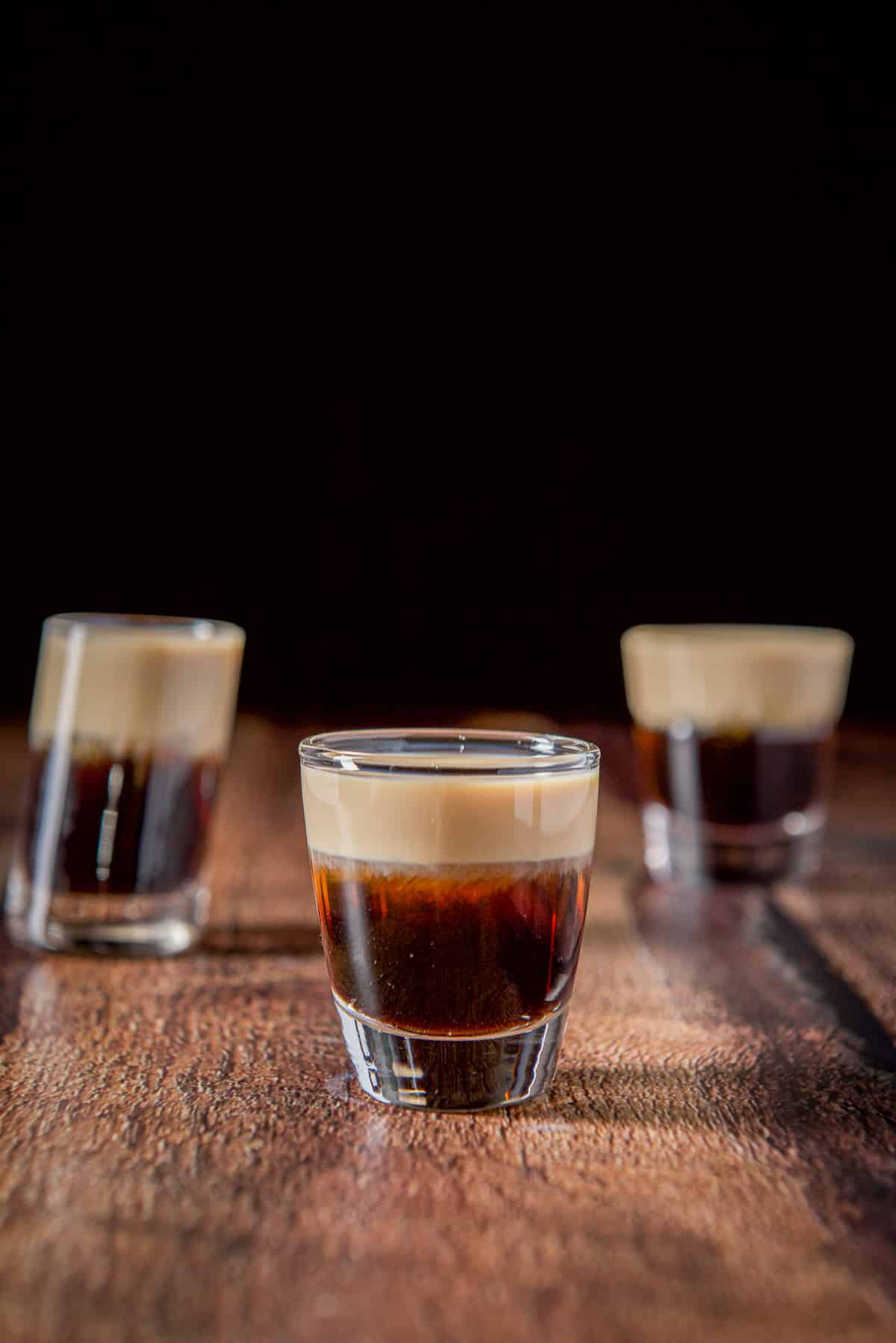 The short glass filled with the layered shot on the wooden table. There are two other glasses behind it