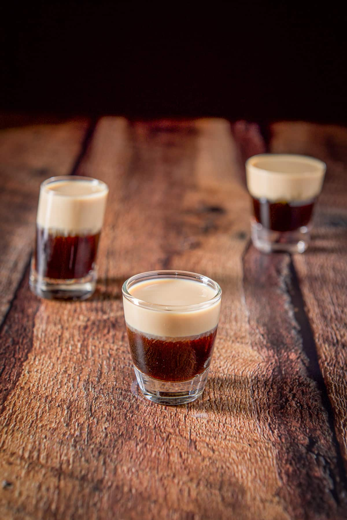 Three glasses filled with a layered shot all on a wooden table